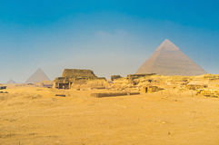 The archaeological site of Giza. The Pyramids of Giza with the ancient ruins on the foreground, Egypt Royalty Free Stock Photos