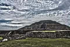 Archaeological site landscaping. Famous and majestuous Mexican archaeological site; sun pyramid during Mexico`s rainy season, green grass and flowers Stock Photos