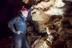 Archaeologist look at the drawing on stone wall in the caves. View of an archaeologist look at the drawing on stone wall in the caves royalty free stock image