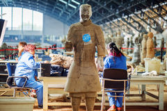 Archaeologists working at excavation of the Terracotta Army. XI`AN, SHAANXI PROVINCE, CHINA - OCTOBER 28, 2015: Chinese archaeologists working at excavation of stock images