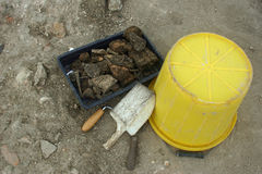Archaeology tools and finds. Which includes a yellow bucket, trowel, shovel and finds tray with bones, pottery and building materials. Background of excavated royalty free stock photography