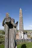 Archangel gravestone before an Ancient round tower. Angel statue before an Ancient round tower and celtic graveyard with cathedral in Ardmore county Waterford Royalty Free Stock Photos