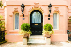 Arched black Door & windows on salmon color home Stock Photos