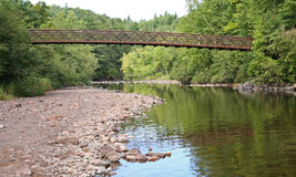 Arched Bridge Above Calm Stream. Arched Footbridge over Rocky Stream in Thick Forest Royalty Free Stock Photography