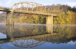 An arched bridge and autumn trees reflected in a river, Tennessee stock image