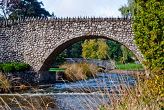Arched bridge made of irregular stones. Over a pleasant, fast-flowing, stream Royalty Free Stock Photography