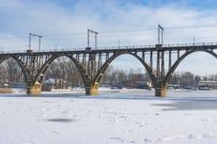 Arched bridge over Dnepr river at winter season in Dnepr city, Ukraine. Classical arched bridge over Dnepr river at winter season in Dnepr city, Ukraine stock image