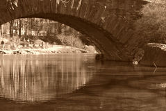 Arched bridge over river. Sepia view of arched stone bridge over river Stock Images