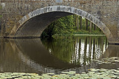 Arched bridge on river the Evre in Loire valley Royalty Free Stock Images