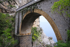 Arched bridge between rocks and sea and sky visible beneath it Royalty Free Stock Photo