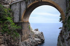 Arched bridge between rocks and sea and sky visible beneath it Royalty Free Stock Image