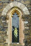 Arched church window. Architectural detail close up of a gothic arched church window with stone faces each side and clear leaded glass royalty free stock photography