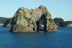 An arched covered with bushes rock rising from the sea. Royalty Free Stock Photos