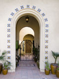 Arched doorway entrance with gate. And potted tropical plants Stock Image