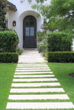 Arched doorway with landscaping. And wall lamps Stock Images