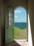 Arched Doorway to Beach. Arched doorway opening onto a grassy beach with sunlight streaming in Royalty Free Stock Photography