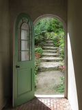 Arched Doorway to Quiet Garden. Arched doorway opening on stone garden stairs with sunlight streaming in Stock Image