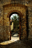 Arched doorway in wall. A view through an arched doorway or entrance in a thick brick and stone wall Stock Image