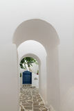 Arched doorways leading to a blue door. Traditional architecture of local villages at Paros island in Greece. Stock Images
