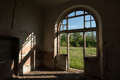 Arched entrance at sunset. Arched entrance to an abandoned train station with broken windows and doors Royalty Free Stock Photo