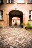 Arched entrance to courtyard on old European building stock photos