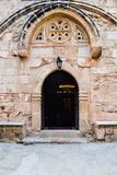 Arched entrance to the old church. Inside lit candles and lamps Royalty Free Stock Photography