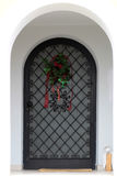Arched front door with bars. Photo closeup of decorated old arched closed front door with black metal bars with holiday wreath and mat over white beige plastered Stock Images