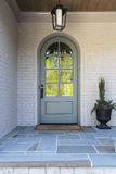 Arched front door with light and plant Royalty Free Stock Photos