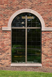 Arched glass window on brown brick wall Stock Photo