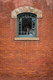Arched Green Window - Center Top. Vintage Arts & Craft 22-pane window in weathered rust-colored brick wall Stock Images