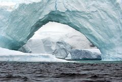 Arched iceberg in the frigid waters of Antarctica. Arched iceberg with cracks at the top grounded in a bay in the frigid waters of Antarctica royalty free stock image