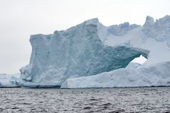 Arched iceberg in the frigid waters of Antarctica. Arched iceberg grounded in a bay in the frigid waters of Antarctica royalty free stock photo