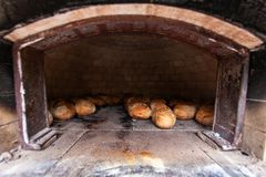 Arched outdoor bread oven made of bricks and clay, full of home-made bread royalty free stock photography