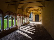 Arched porch with white stone columns in the courtyard of a Bene. Porch with white stone columns in the courtyard of a Benedictine abbey Stock Photos