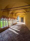 Arched porch with white stone columns in the courtyard of a Bene. Porch with white stone columns in the courtyard of a Benedictine abbey Stock Images
