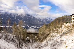 Arched railroad bridge near mountain. Beautiful mountains covered in snow and clouds with arched railroad bridge at bottom surrounded by trees Royalty Free Stock Images