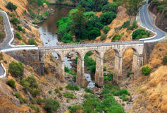 Arched road bridge. With high stone arches crossing a river bed in mountainous countryside with tarred roads Royalty Free Stock Photo