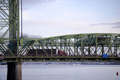Arched section of bridge with support and moving red semi truck Stock Photos