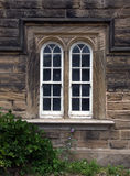 Arched sliding sash windows. A pair of arched sliding sash windows in stone frames with stone mullions Stock Photos