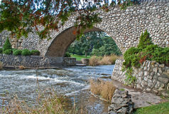 Arched stone bridge. Arched bridge made of irregular stones over a pleasant stream Stock Photography