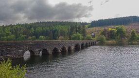 Arched, Stone Bridge Over a Lake. An old, stone bridge, with arches, spanning a tranquil lake Royalty Free Stock Image