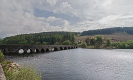 Arched, Stone Bridge Over a Lake. An old, stone bridge, with arches, spanning a tranquil lake Royalty Free Stock Photos