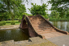 Arched stone bridge over water in sunny spring Royalty Free Stock Image
