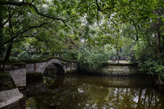 Arched stone bridge in pond of verdant summer Royalty Free Stock Photo