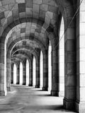 The arched stone colonnade. Old arched stone colonnade curved to the left. Black and white image Stock Photos