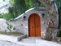 Arched stone courtyard entry wall with arched wooden door Stock Photo
