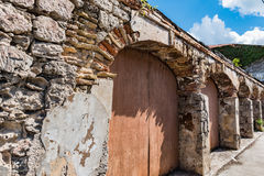Arched stone doorways with carriage doors along urban street on. The island of St. Croix Stock Photos