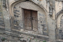 Arched stone wall with old door Stock Image