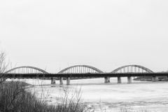 Arched traffic bridge over a river Stock Images