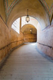 An arched tunnel with wooden floor in an old castle with sunlight from the window, Czech royalty free stock image